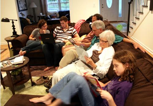 family on sofa doing digital activities